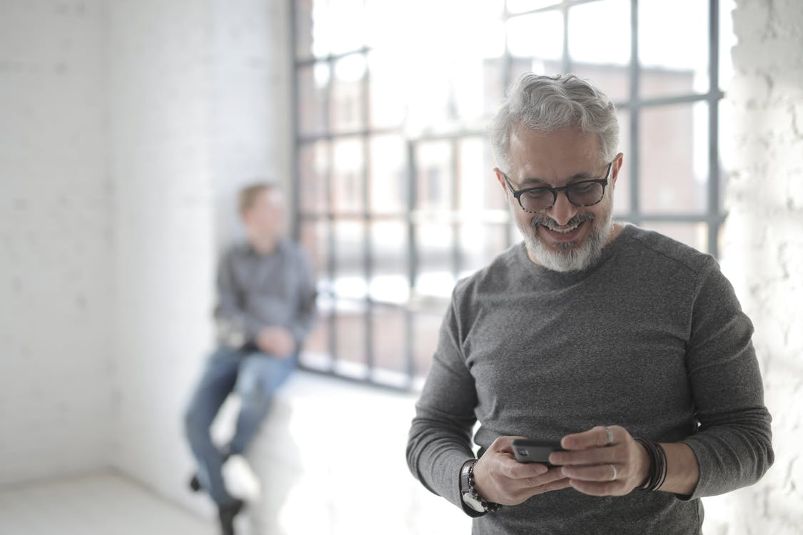 Middle aged bearded man in casual clothes standing with mobile phone while looking at screen and smiling during break in modern workspace