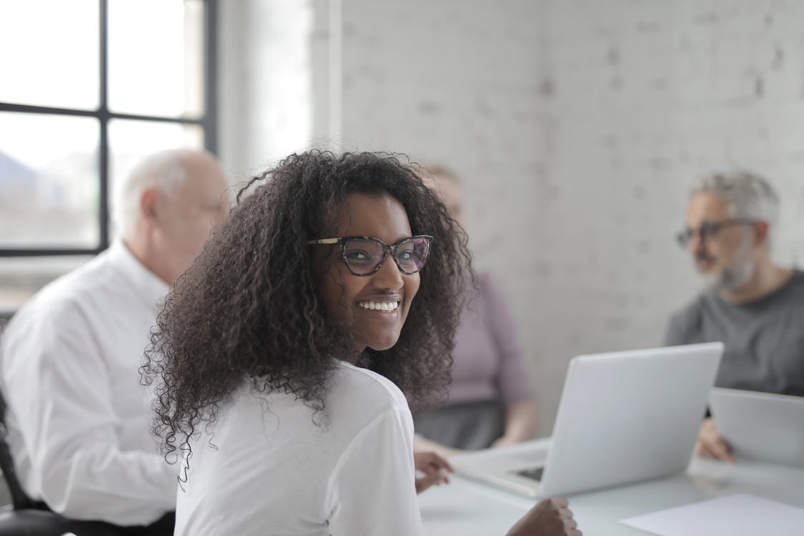 Smiling woman working in office with coworkers