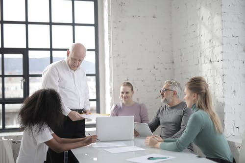 Serious elderly man wearing formal clothes standing while explaining business project with colleagues and discussing details during brainstorm at modern office