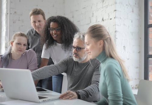 Cheerful diverse colleagues working on laptop in office