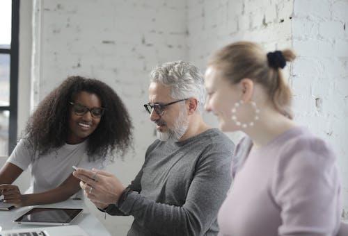 Man in Gray Sweater Sitting Beside Women