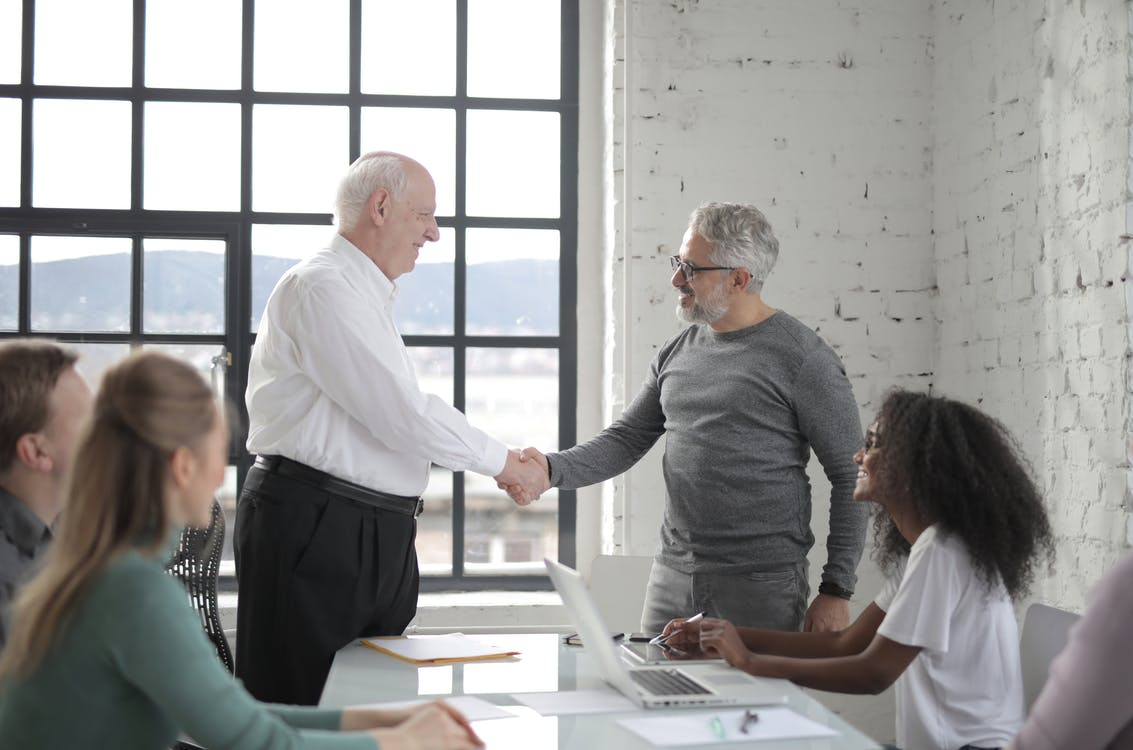 Group of diverse coworkers in office man middle aged and man senior shacking hands while working on project with colleagues
