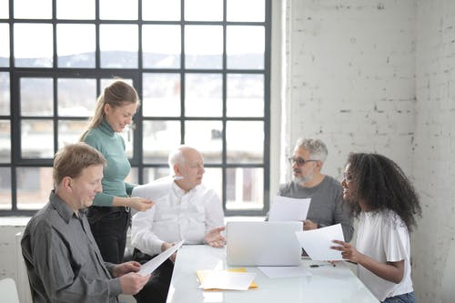 Multiracial coworkers of different ages brainstorming together in office