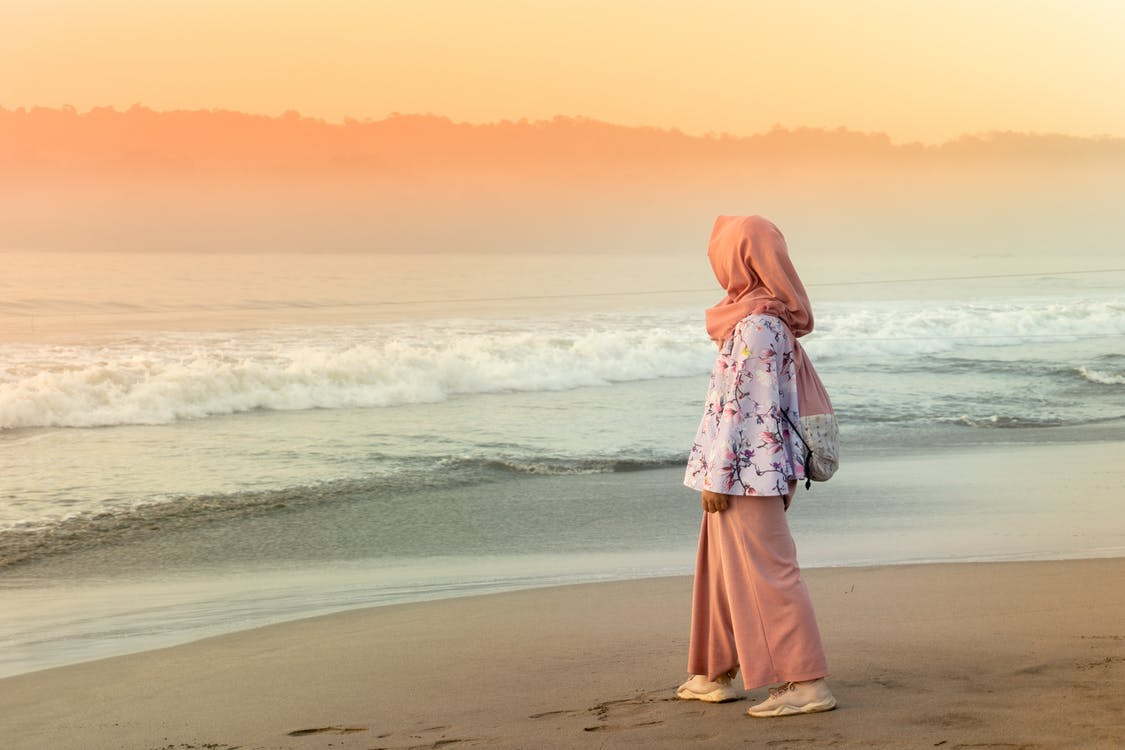 Woman in Orange Hijab Standing on Beach during Sunset