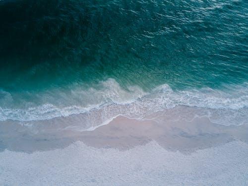 Body of Water Beside Beach Sand