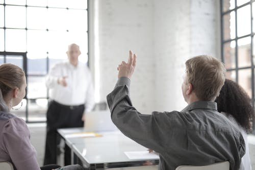 Male employee raising hand for asking question at conference in office boardroom