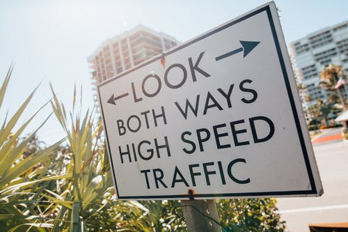 Direction sign with arrow and look both ways high speed traffic text placed on sidewalk near tropical plants against modern city buildings