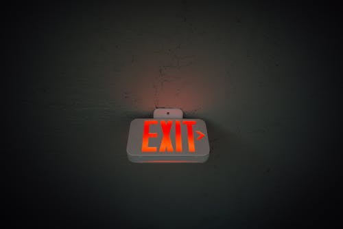 Exit sign hanging on ceiling in public area