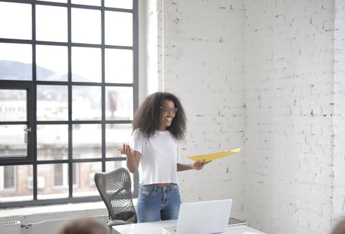 Cheerful young black female speaker presenting ideas at meeting in office workspace