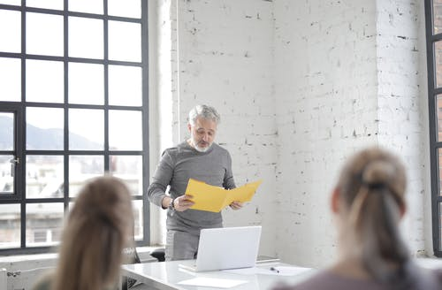 Focused aged gray haired bearded male speaker in casual wear presenting ideas to colleagues in conference room at meeting while standing at table with laptop