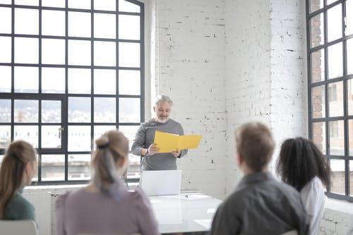 Senior gray haired bearded male coach presenting ideas at diverse group meeting in modern office