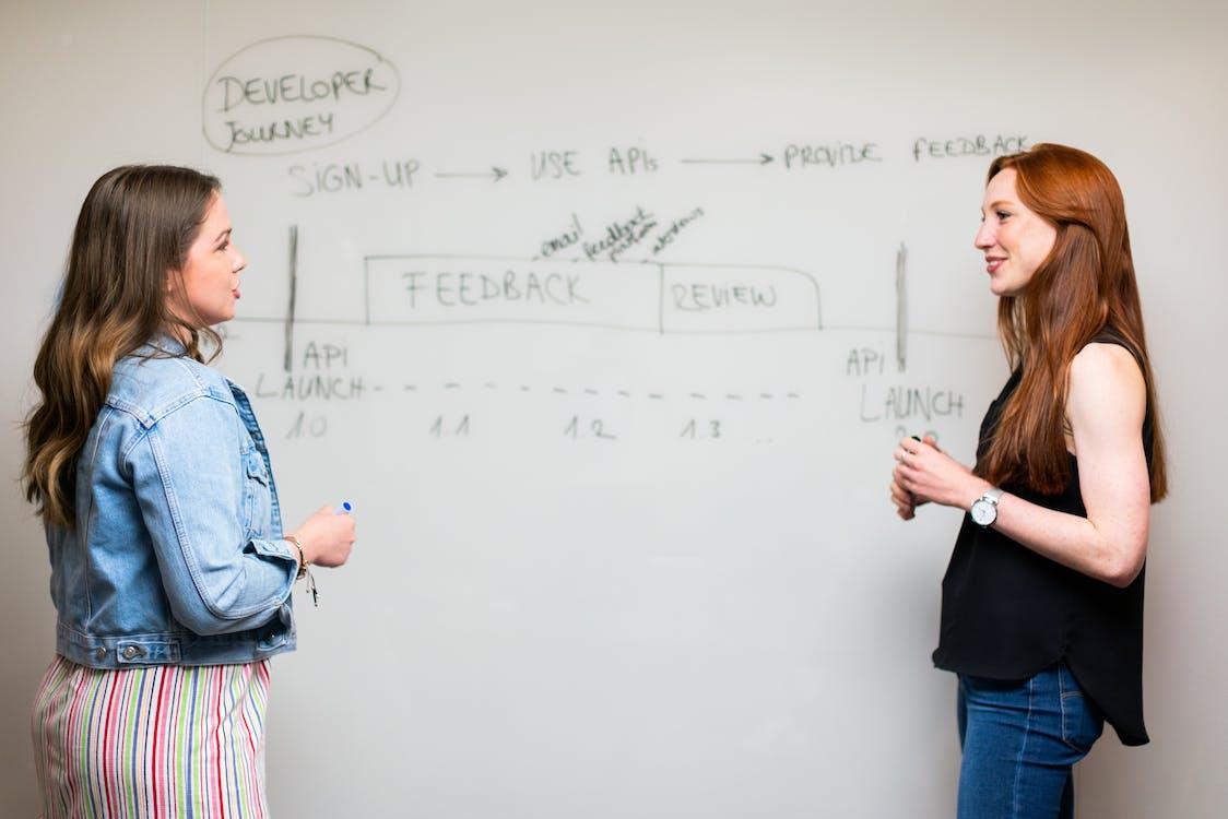 Photo Of Women Talking Beside Whiteboard