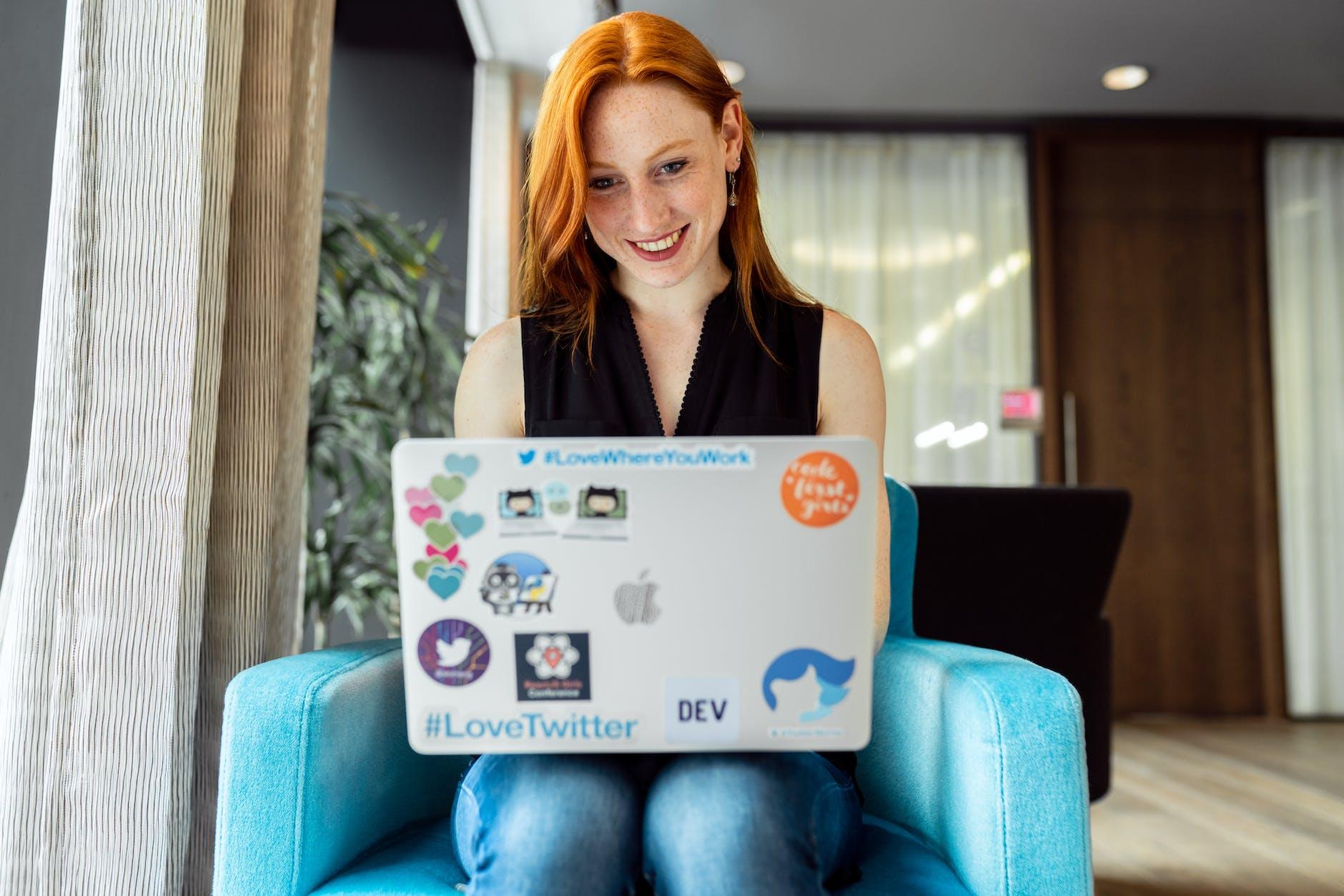Women sat down, smiling at her laptop