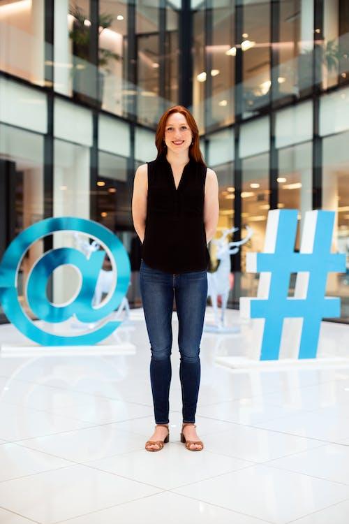 Wanita Dengan Kemeja Tanpa Lengan Hitam Dan Jeans Denim Biru Berdiri Di Ubin Lantai Putih