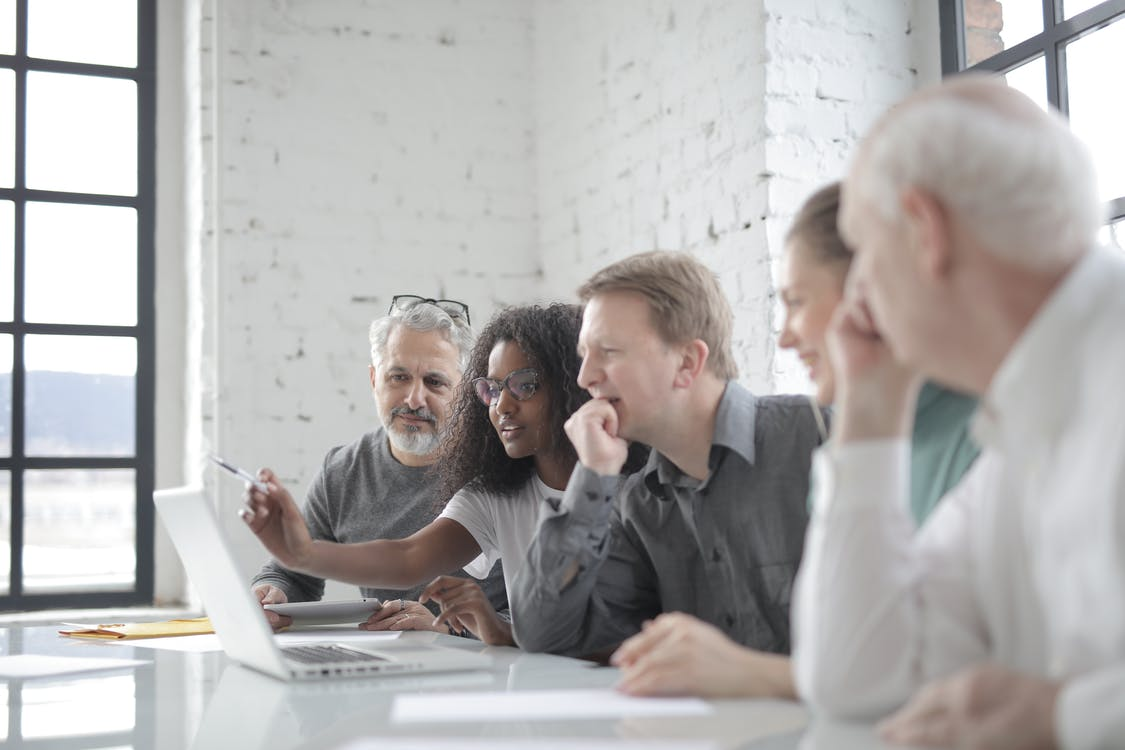 Content multiracial coworkers talking about project and watching laptop