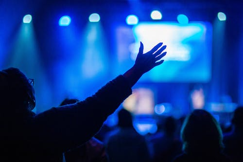 Back view of crop unrecognizable woman in eyeglasses with outstretched arms enjoying concert in dark club with neon spotlights