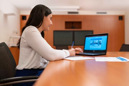Woman in White Long Sleeve Shirt Using Black Laptop