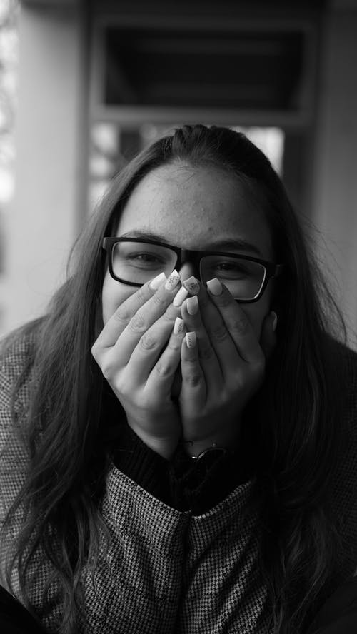 Grayscale Photo of Woman Wearing Black Framed Eyeglasses Covering Her Mouth with Her Hands