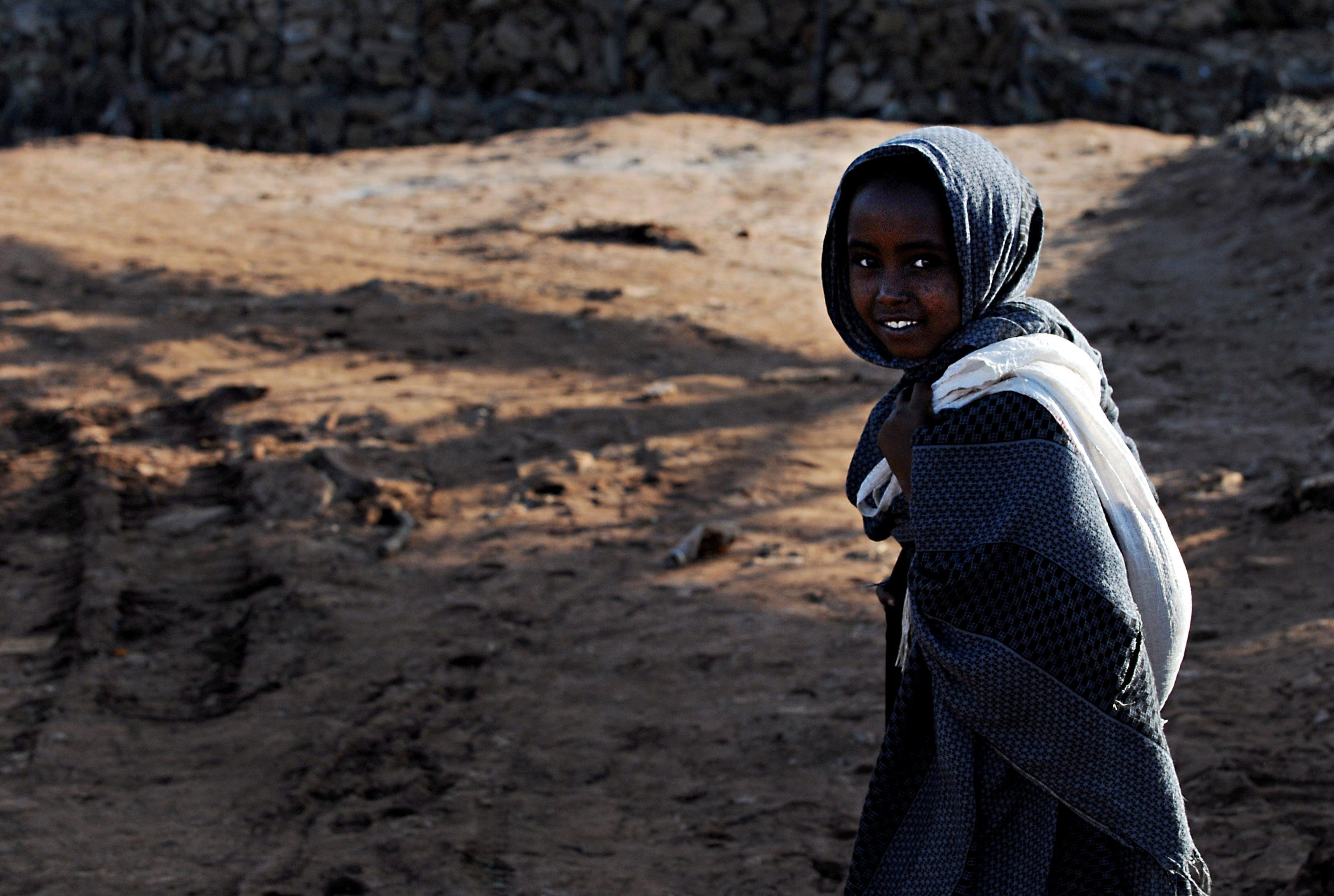 Smiling Child in Black Dress Shirt Walking on Brown Sand during Daytime