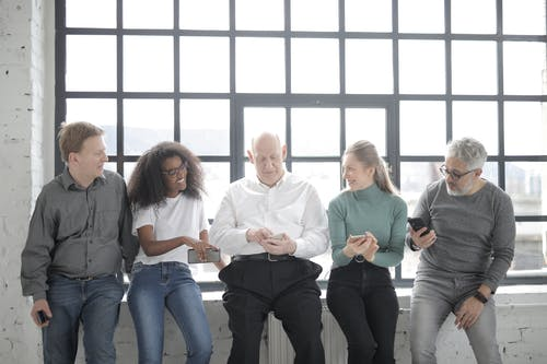 A Group Of People Sitting Beside A Steel Framed Window While Holding Their Phones