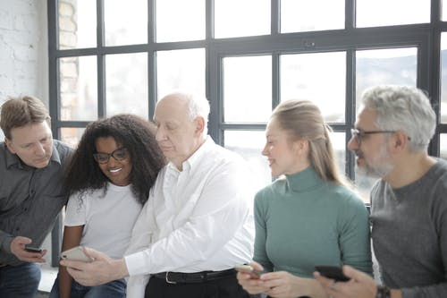 Smiling multiracial colleagues surfing internet on smartphones during break