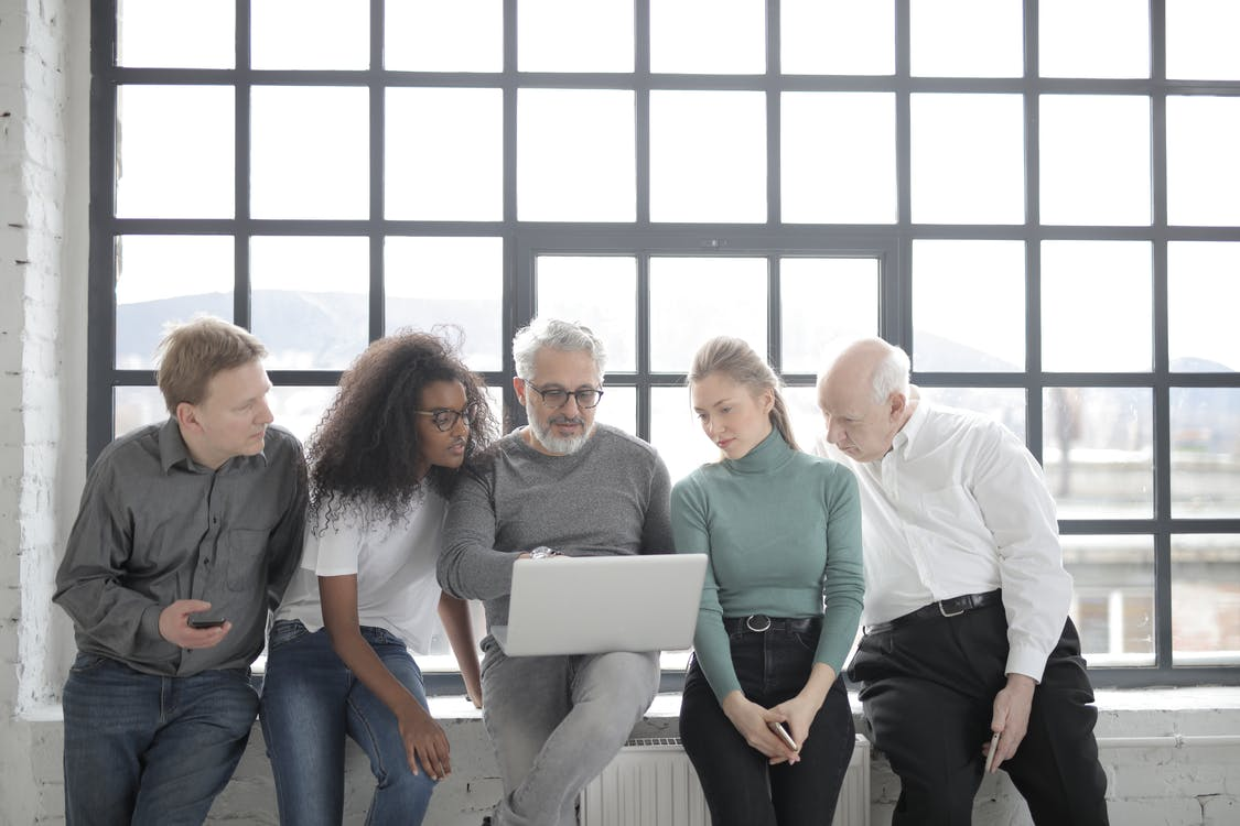 Group of People Sitting By The Window And Looking At A Laptop