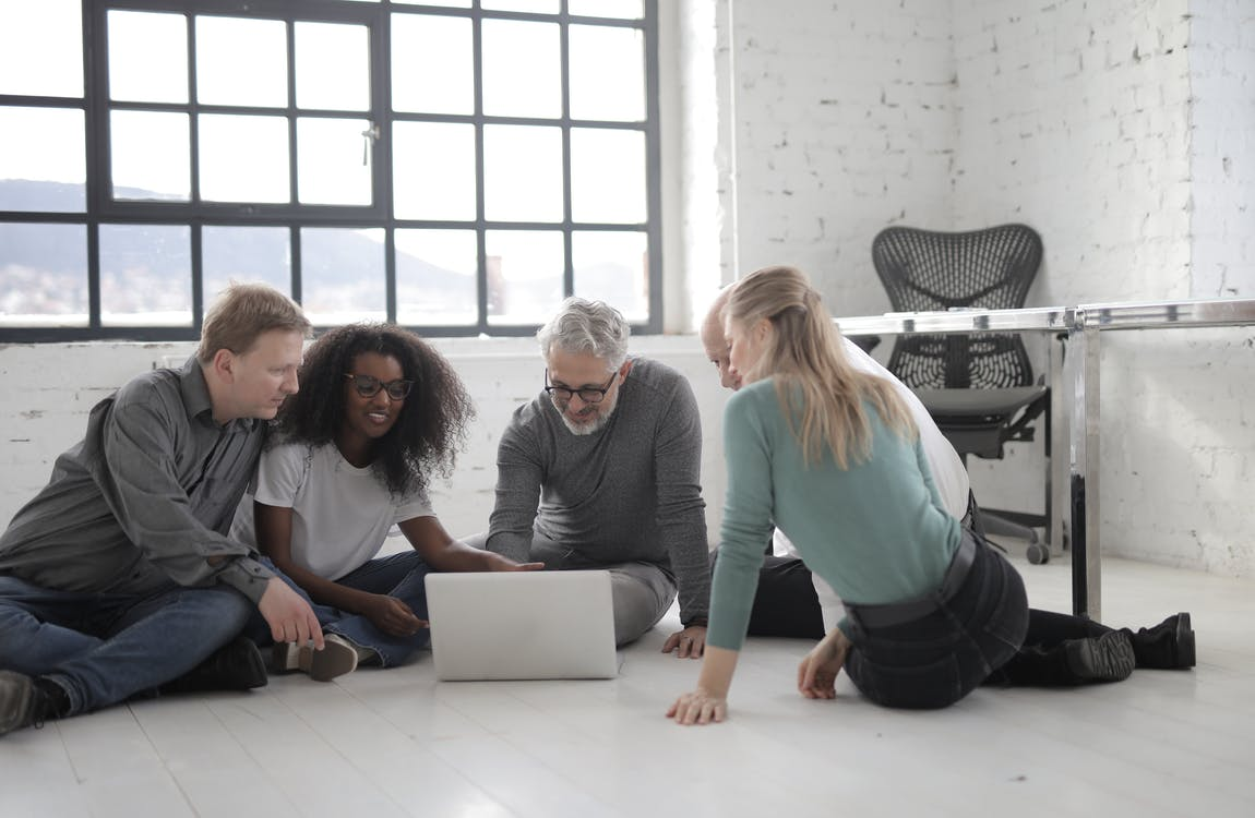 Group Of People Working While Seated On The Floor