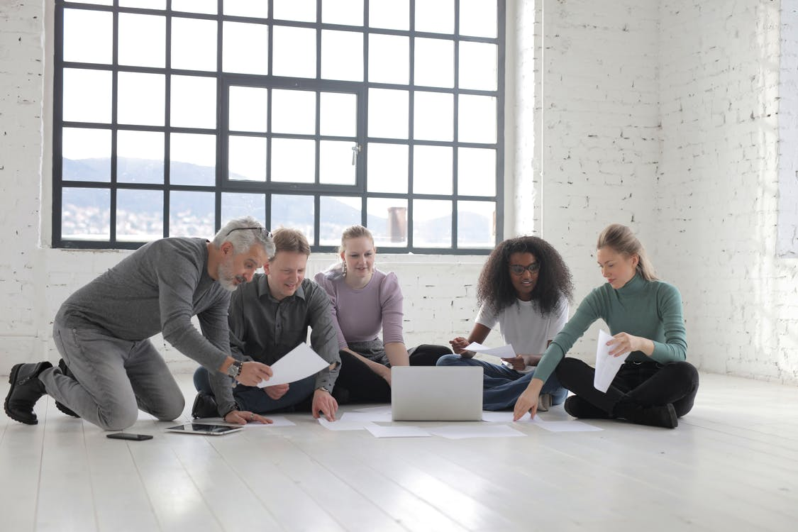 Group of People Sitting On The Floor While Working