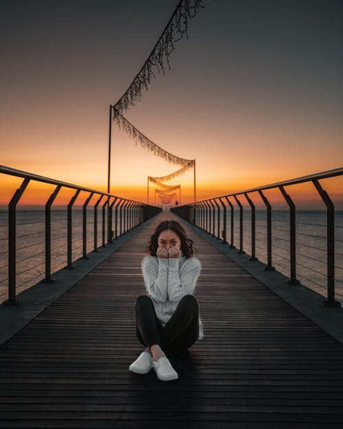 Woman In White Long Sleeve Shirt Sitting On Wooden Dock During Sunset