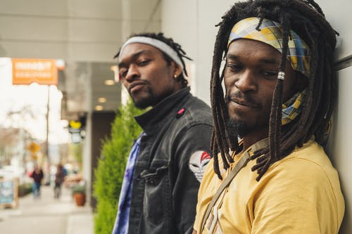 Young black men with dreadlocks standing near building entrance
