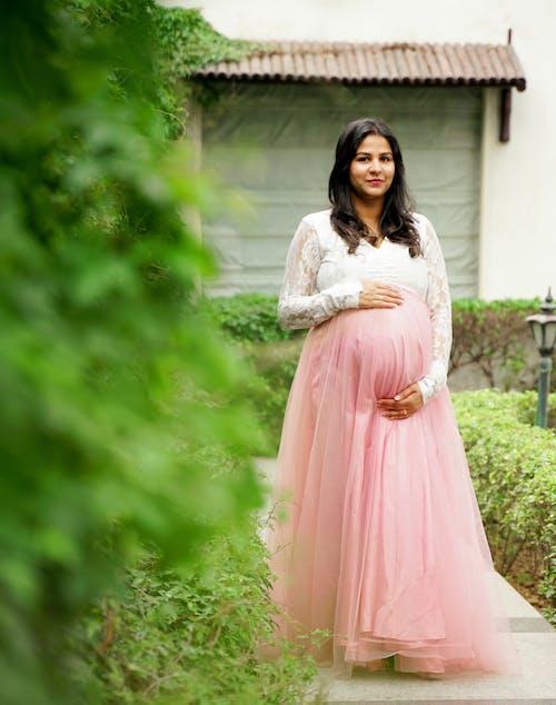 Woman In Pink Dress Standing Near Green Plants