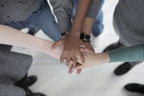 Crop from above of faceless multiracial friends in casual clothes uniting hands after coming to agreement while standing on light grey ceramic floor