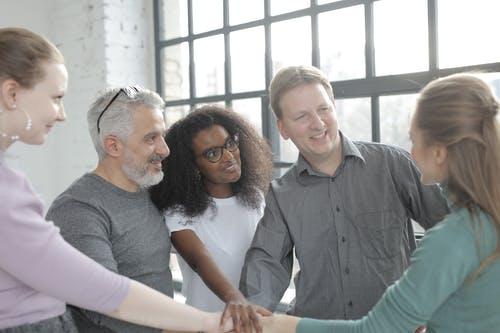Cheerful diverse colleagues joining hands after coming to agreement