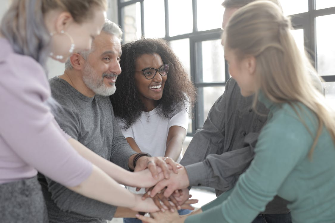 Content multiethnic colleagues joining hands after coming to agreement