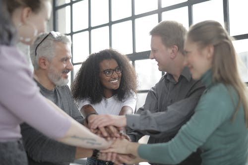 Happy multiracial coworkers uniting hands after making decision