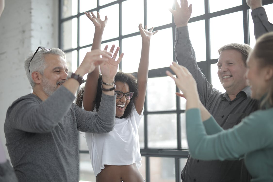 Group of happy multiracial friends raising hands and smiling