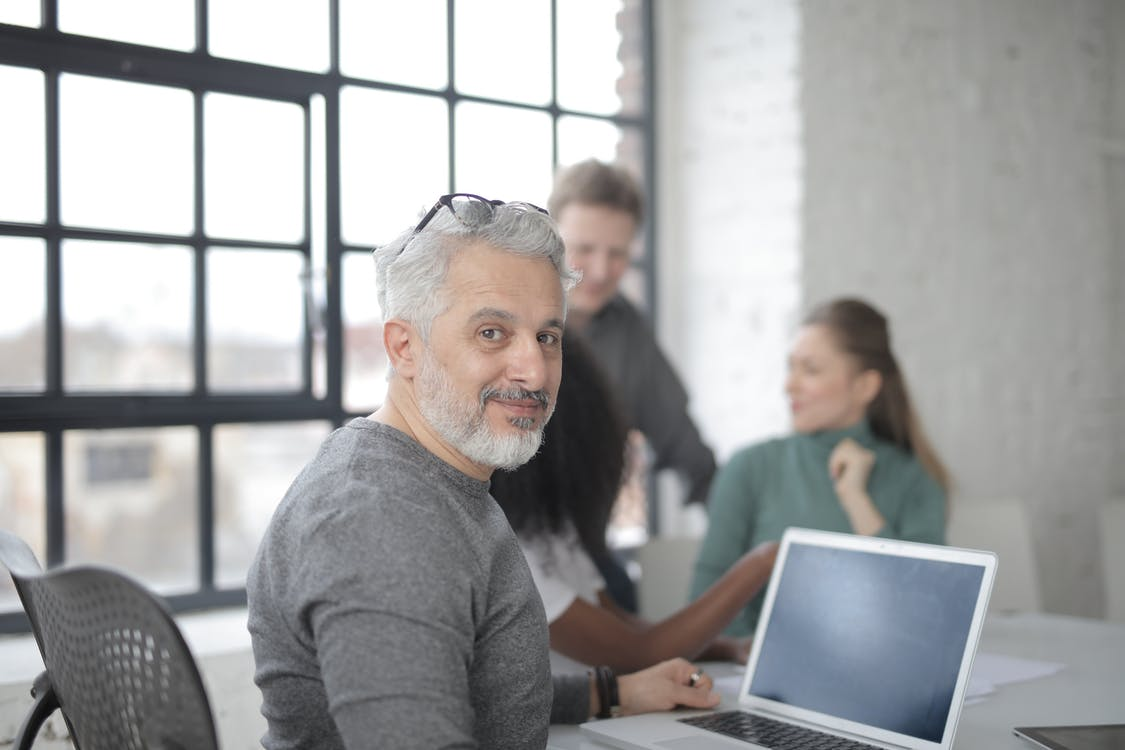Cheerful male worker sitting with laptop and multiethnic coworkers