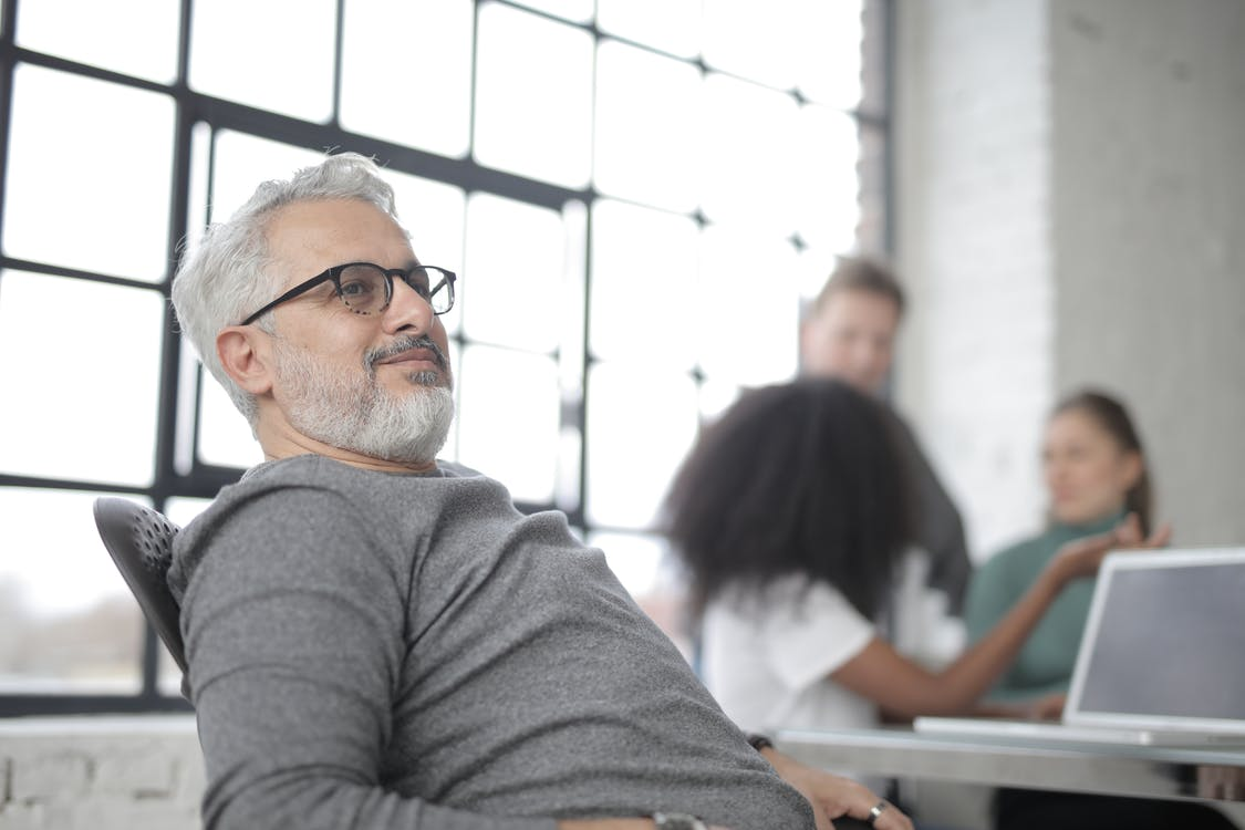 Satisfied gray haired bearded businessman with laptop against diverse colleagues