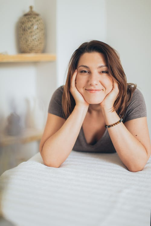 Woman in Gray Shirt Lying on a Bed