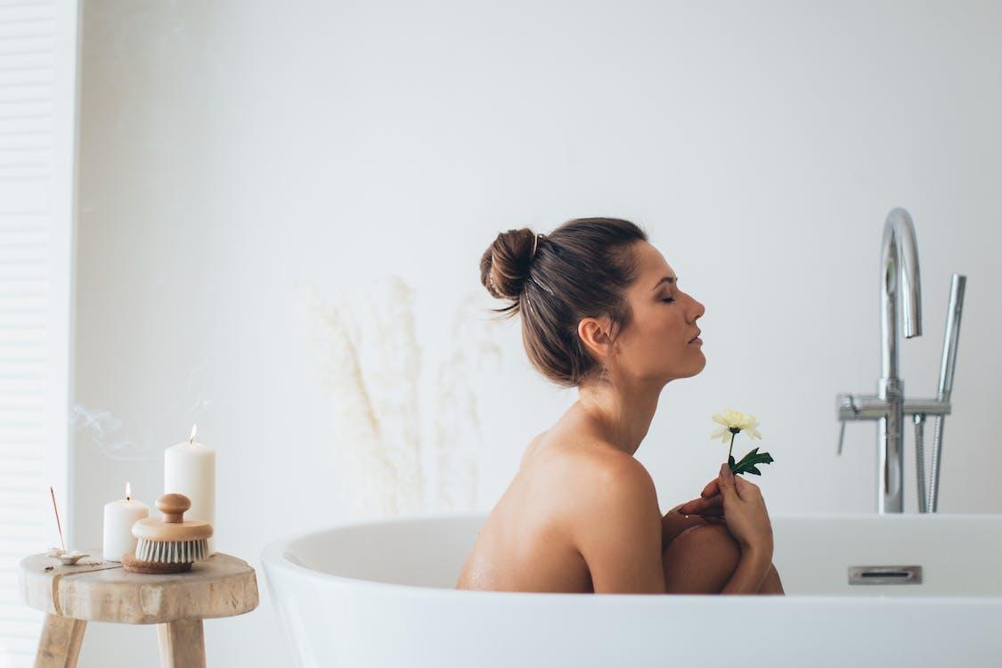 Topless Woman Sitting on White Ceramic Bathtub Holding Flower