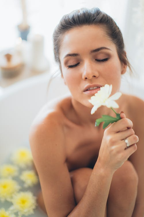 Topless Woman Holding White Flower