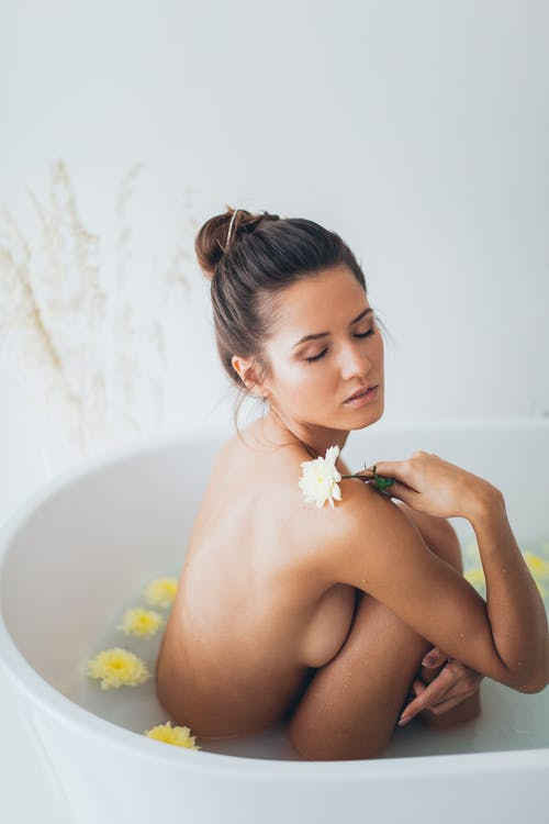 Topless Woman in Bathtub With White Flower