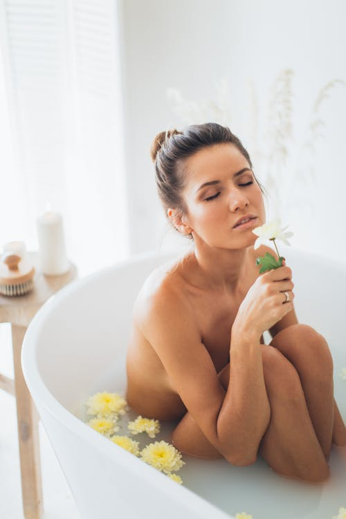 Topless Woman Sitting on Bathtub With Yellow Flowers