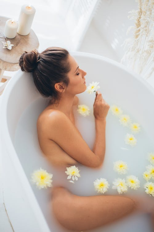 Topless Woman in Bathtub With White Daisy Flowers