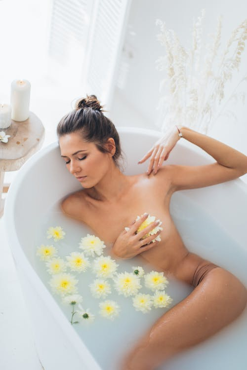 Nude Woman Lying in Bathtub With Water and Flowers