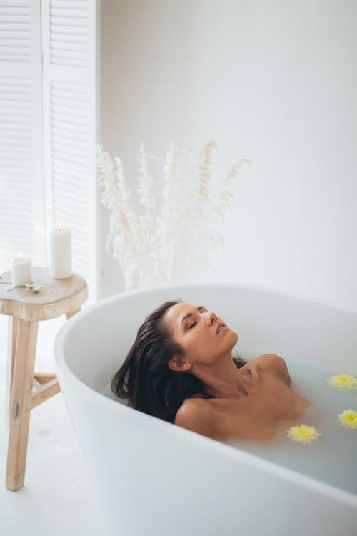 Woman Lying in Bathtub With Water