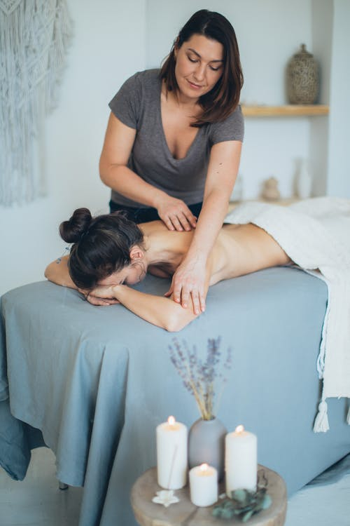 Woman Lying on Bed While Having A Massage