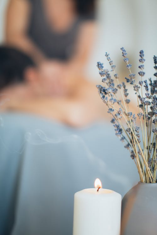 Lavender Flowers And Lighted Candle