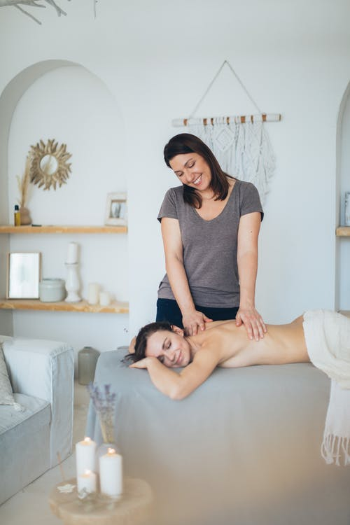 Happy relaxed topless woman getting spa procedures and resting on table while smiling massage therapist massaging back of client in cozy room