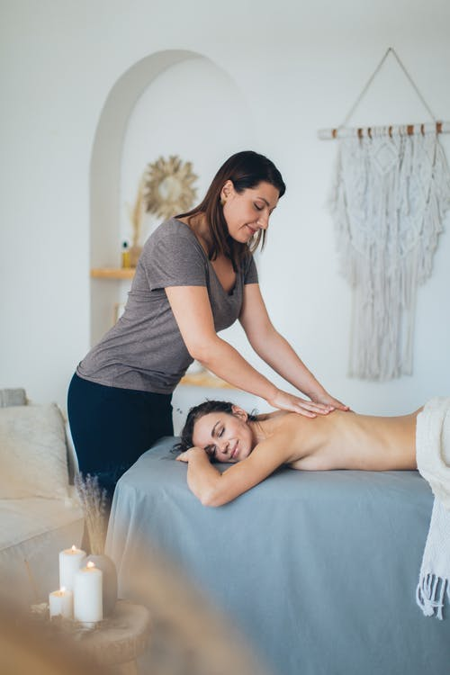 Woman in Gray T-shirt and Black Pants Massaging Topless Woman Lying on Bed